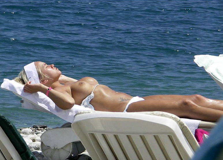 Topless tattooed girlfriend caught tanning at the beach by indiscreet paparazzi