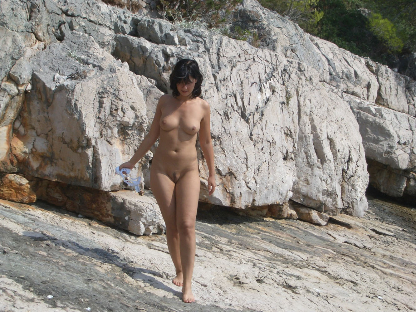 Beautiful brunette nude on the rocky beach